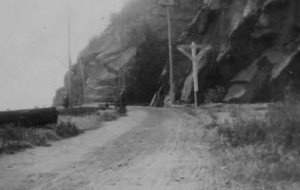 The old Shore Road, looking north. The road does not go through the tunnel, which was rail only at this time. Travelers would turn left toward the river, crossing the tracks coming from the tunnel.